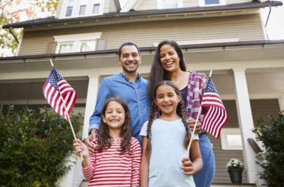 family-with-daughters-holding-american-flags