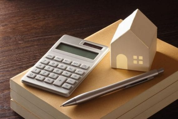 calculator-pen-and-model-house-on-stack-of-books