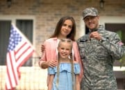 Military family outside of new home with keys